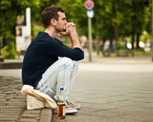 Muškarac sedi na trotoaru
